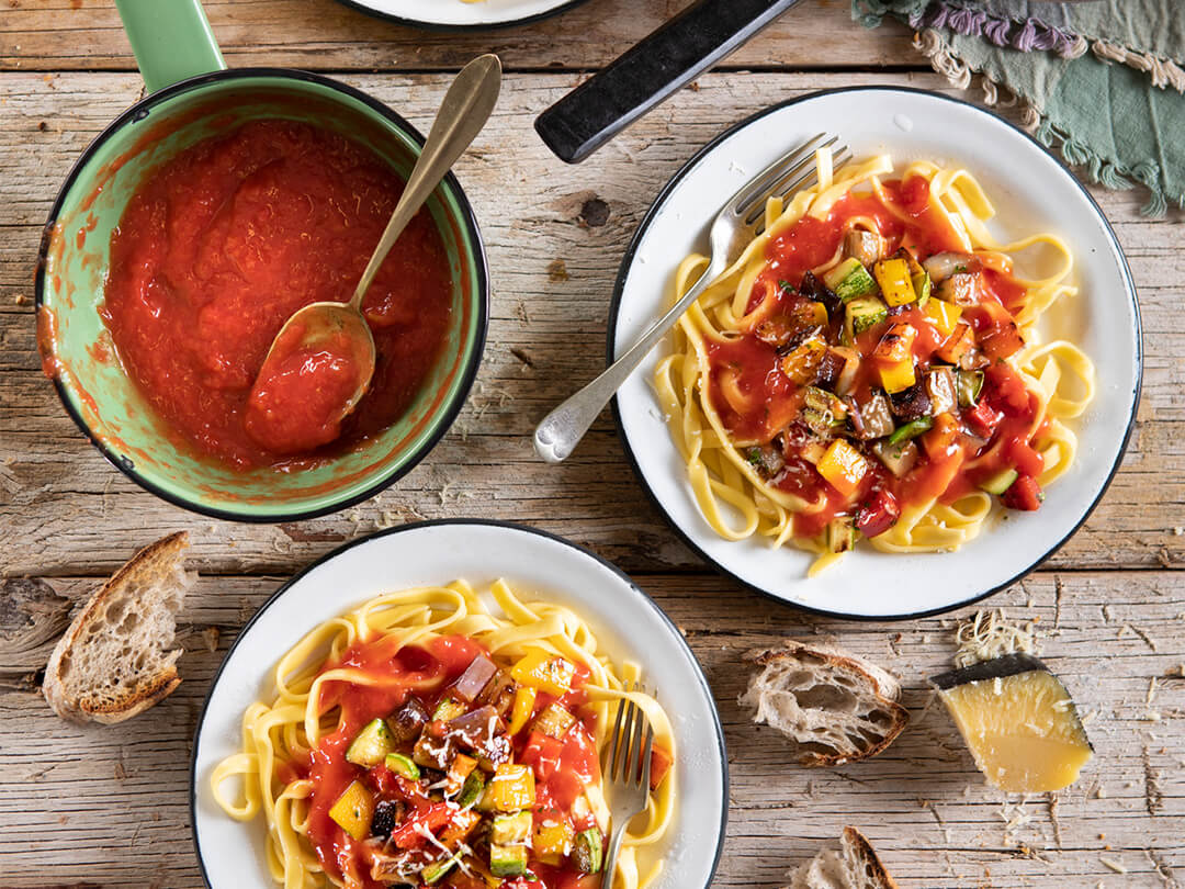 Fideos con puré de tomates y verduras salteadas