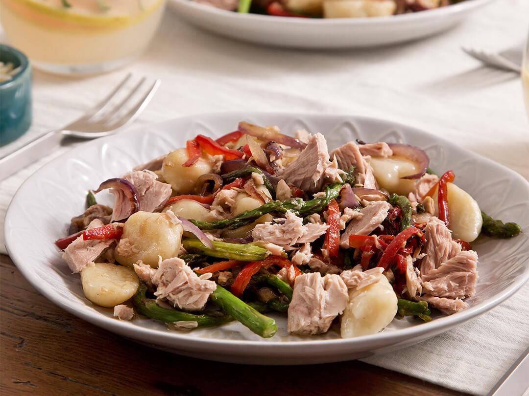 Ñoquis de papa con atún, espárragos, morrones, cebolla morada y aceite de oliva