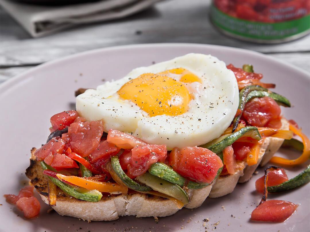 Bruschetta de vegetales salteados, con tomate cubeteado y huevo frito