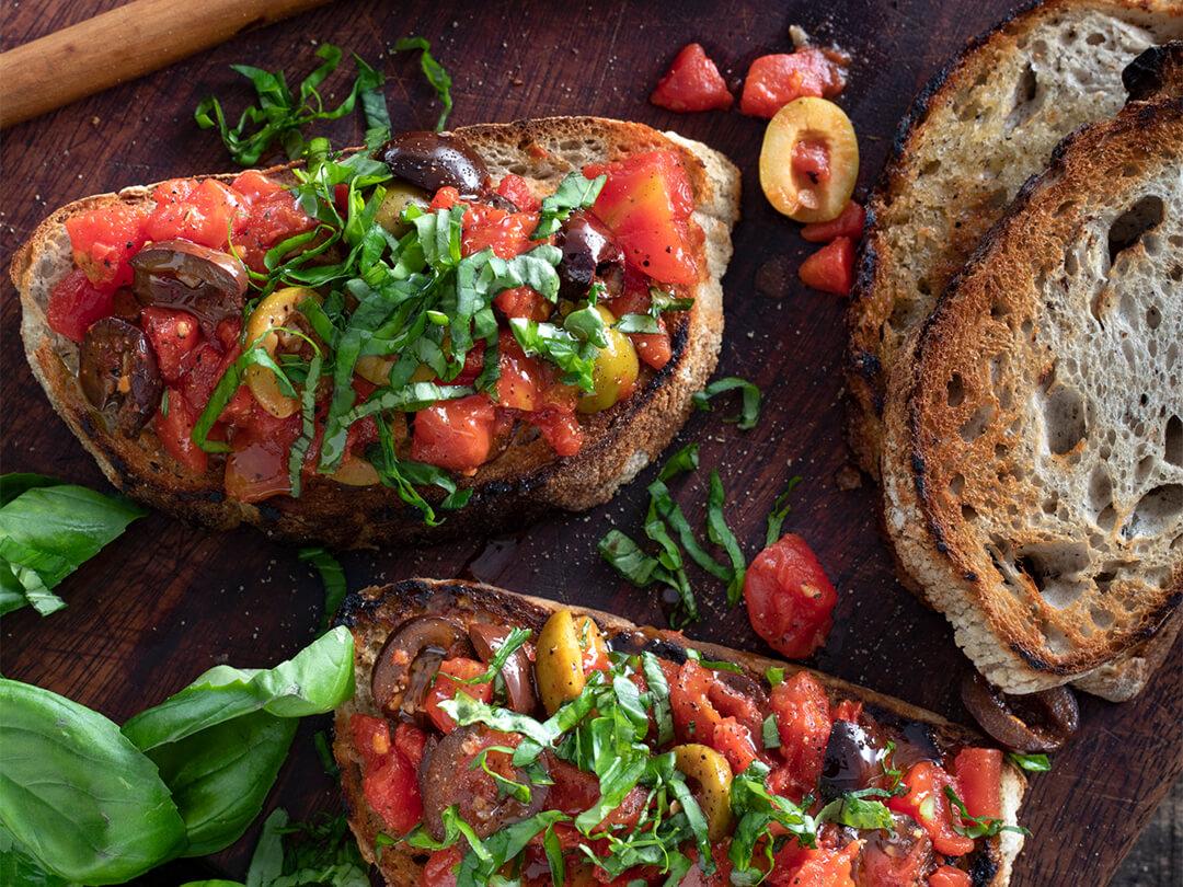 Bruschetta de tomate cubeteado con cubierta de aceitunas, hojas de albahaca y aceite de oliva