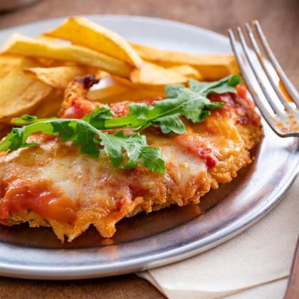 Milanesitas de pollo a la napolitana con salsa portuguesa y rúcula